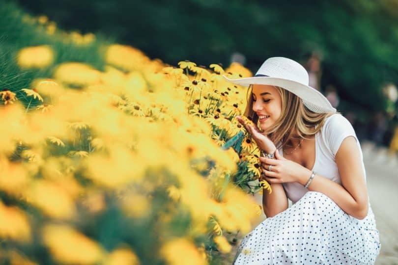 Mulher jovem sorrindo ao lado de um canteiro de flores amarelas.