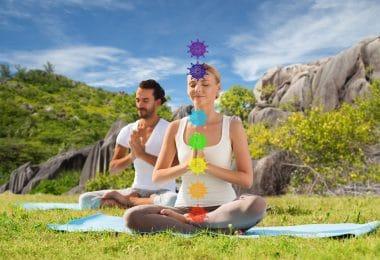 casal meditando na posição de lótus com sete símbolos de chakra sobre fundo de natureza