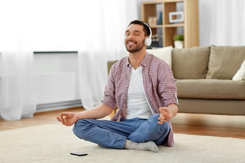 Homem sentado na sala de estar, com as pernas cruzadas e fones de ouvido, meditando.