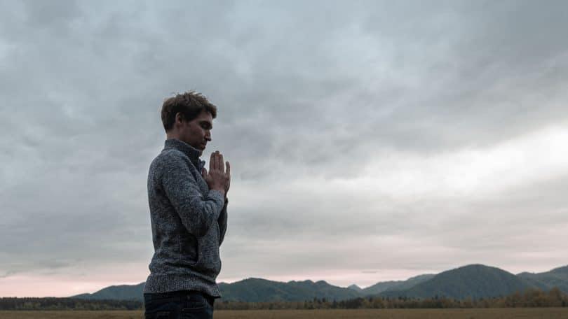 Homem jovem, em pé perto de montanhas, com as mãos cruzadas em sinal de oração, representando o despertar da essência.