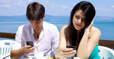 Casal tomando café da manhã cada um com seu celular