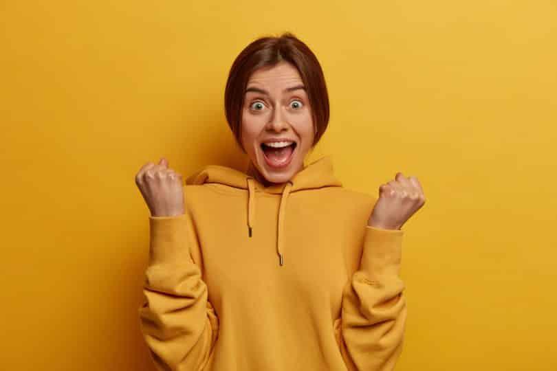 Uma garota surpresa fecha os punhos e olha para a câmera, enquanto usa um moletom amarelo casual