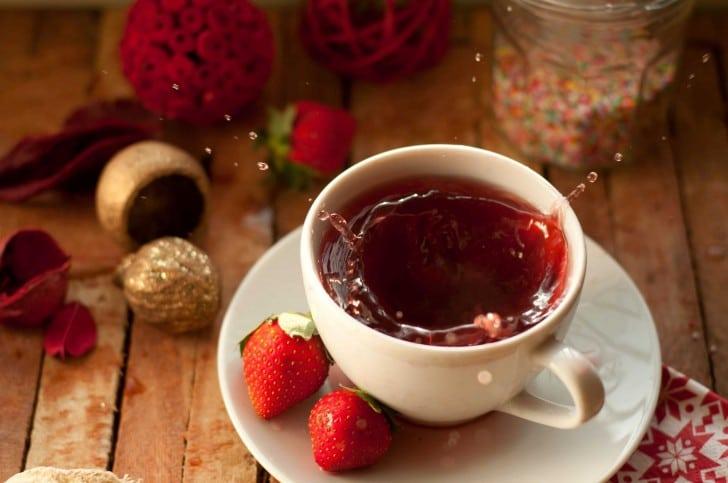 Xícara de chá em pires com morangos