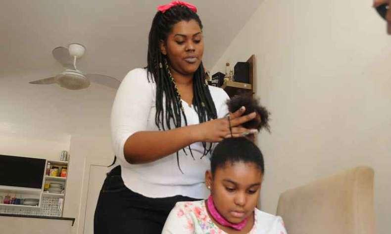 Mulher arrumando cabelo da filha
