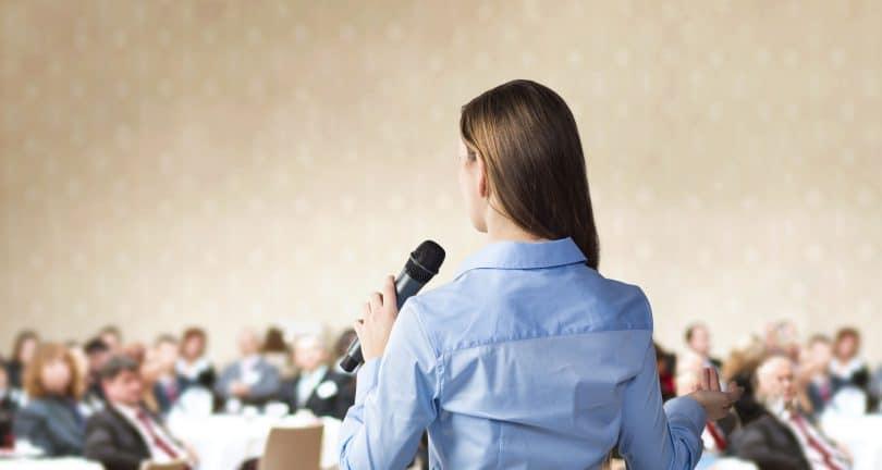 Mulher jovem, de costas, em pé em um púlpito, segurando um microfone, falando em público.