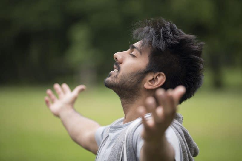Homem de pé com os braços levantados ao ar livre