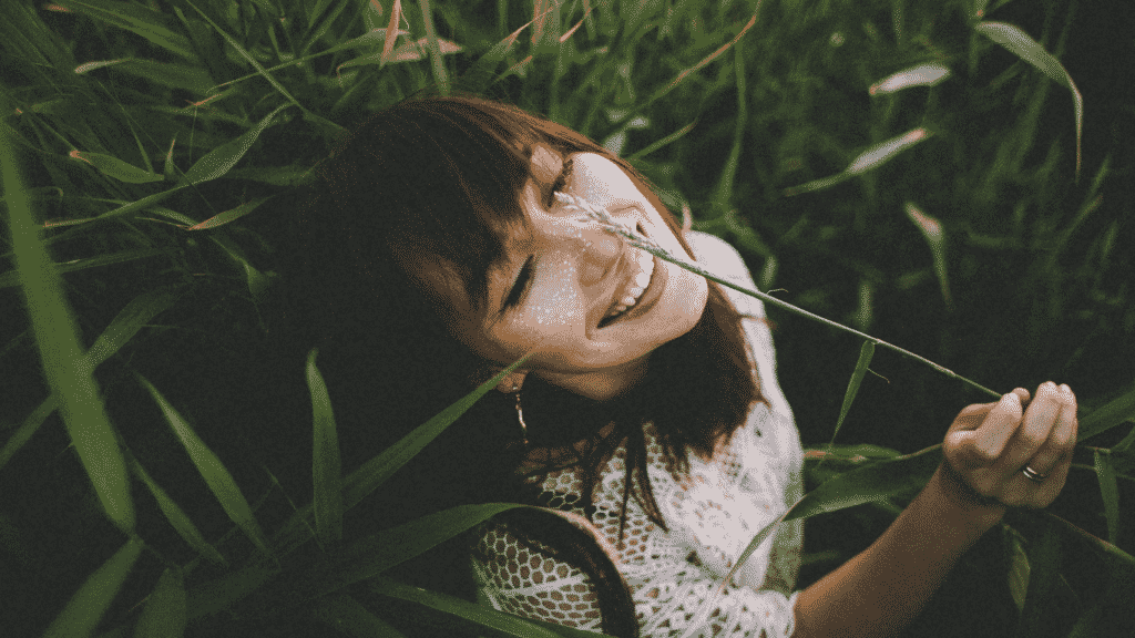 Mulher sorrindo no meio da mata