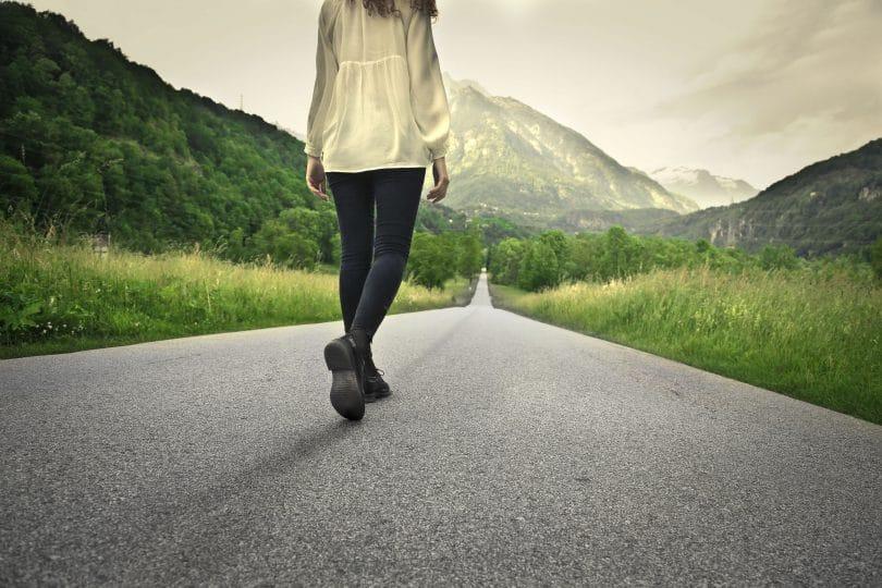 Mulher caminhando em estrada
