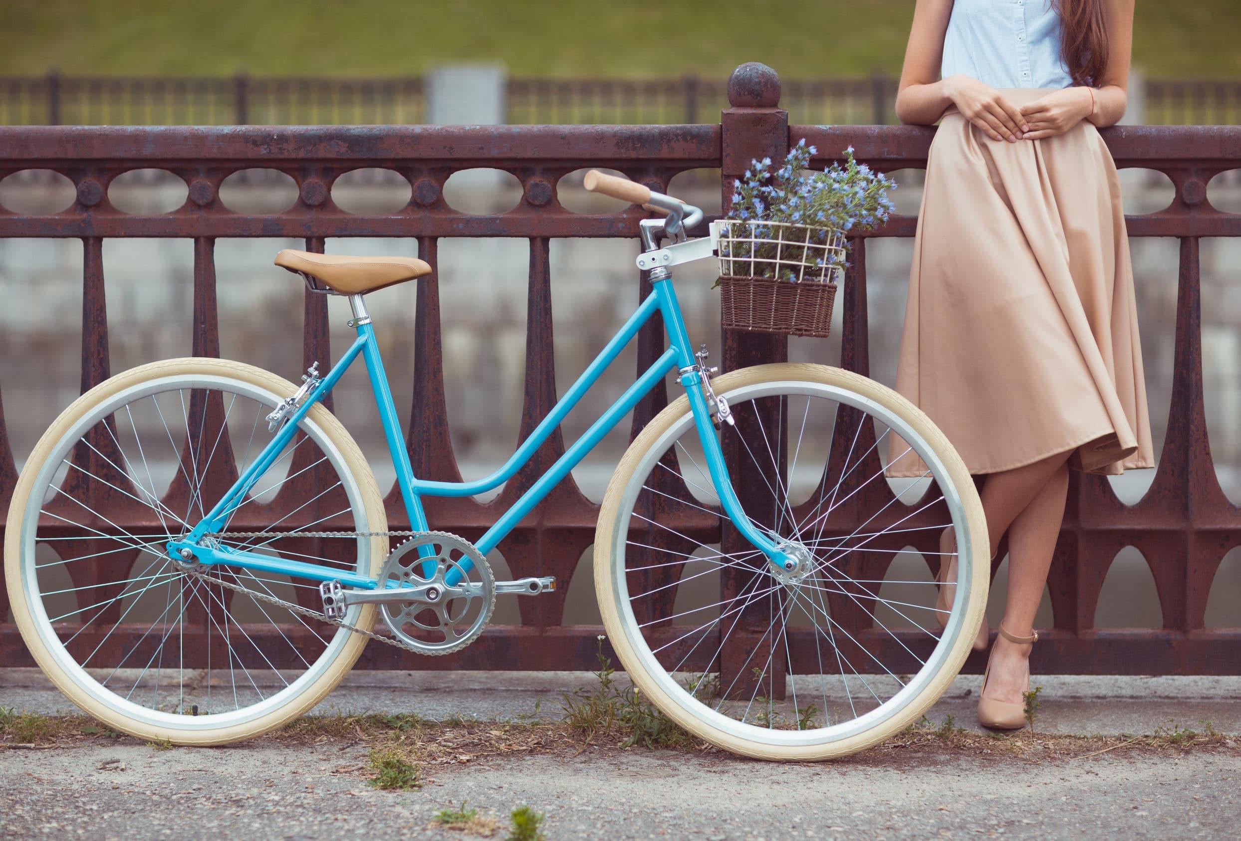 Bicicleta azul com flores no cesto do guidão ao lado de uma mulher.