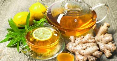 Xícara de chá de gengibre com mel e limão na mesa de madeira