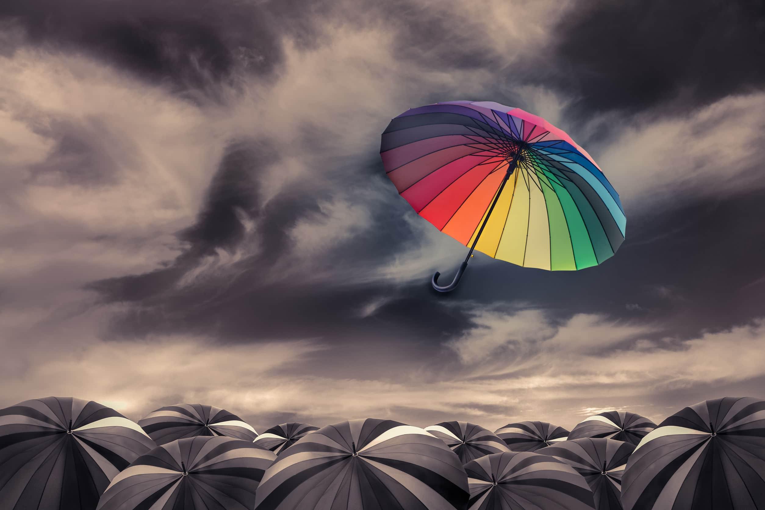 Guarda-chuva colorido voando sobre guarda-chuvas escuro.
