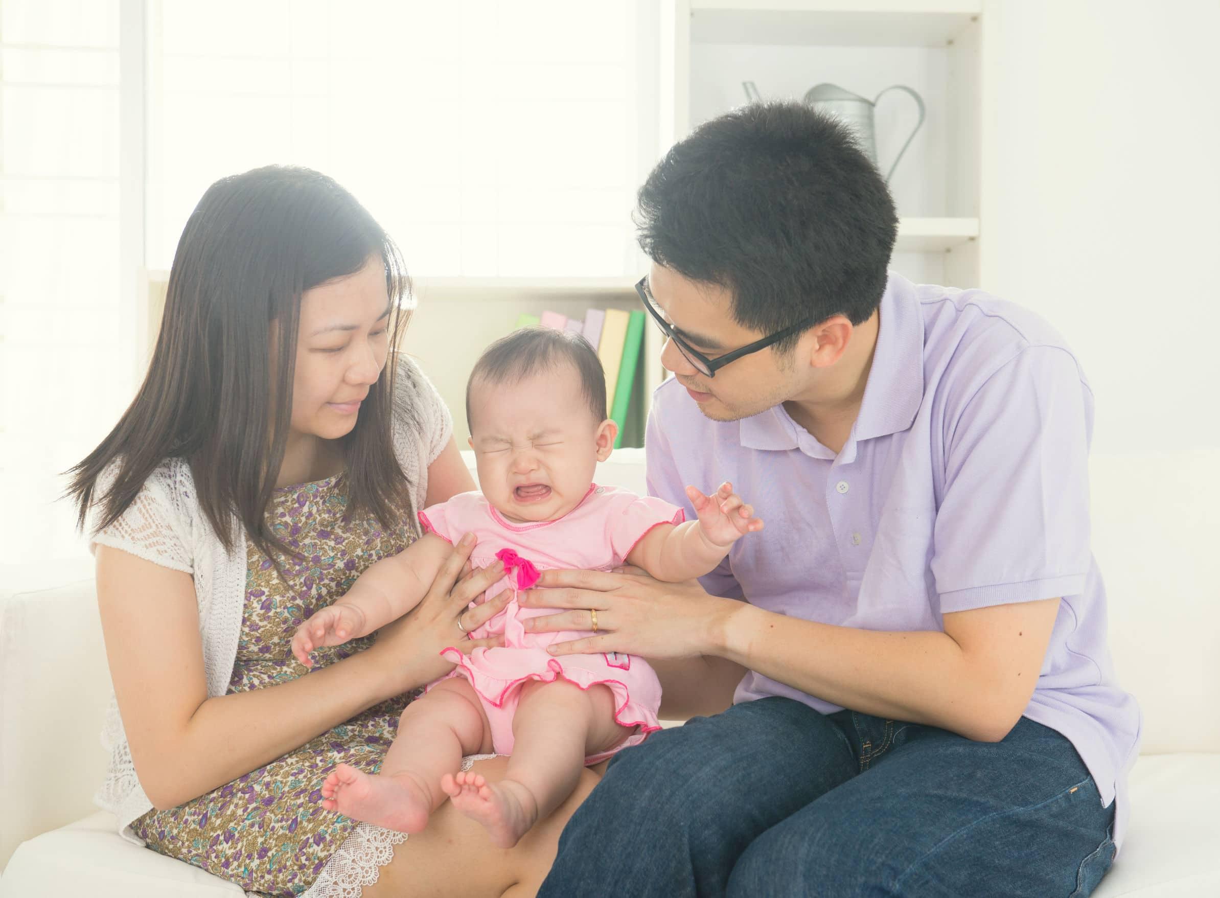 Família de pai, mãe e bebê chorando no colo da mãe.