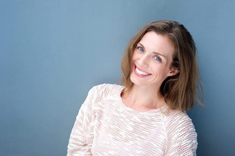 Foto de mulher branca, com mais de 40 anos, sorrindo em pé na frente de um fundo azul