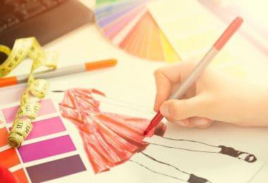 Mão de pessoa desenhando um vestido vermelho em um bloco de folhas bege.