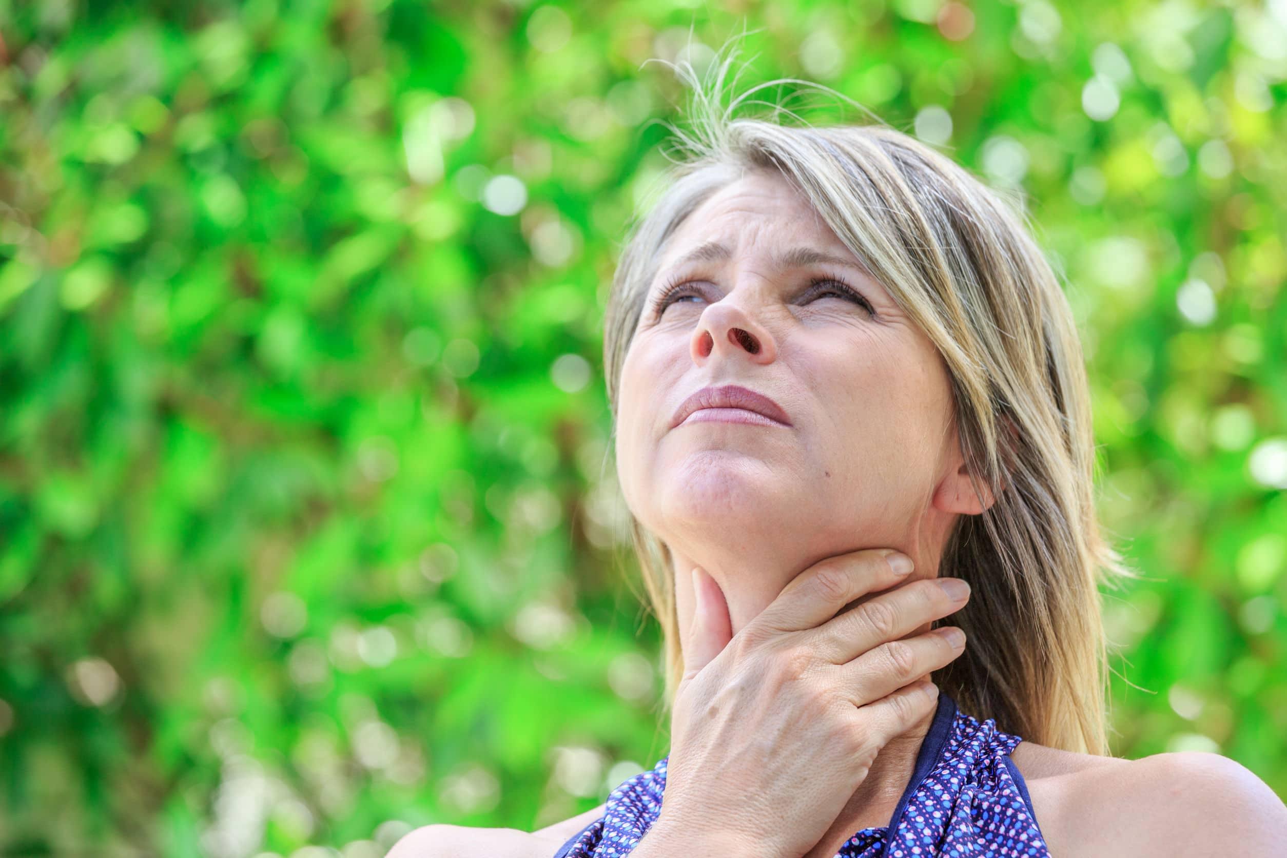 Mulher com as mãos na região da garganta e expressão de dor.