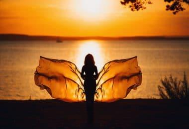 Silhueta de uma mulher diante do pôr do sol em frente ao mar.
