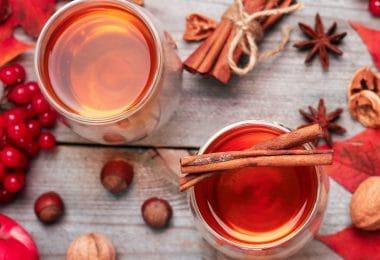 Copos de chá de canela com canelas vista de cima em meda de madeira