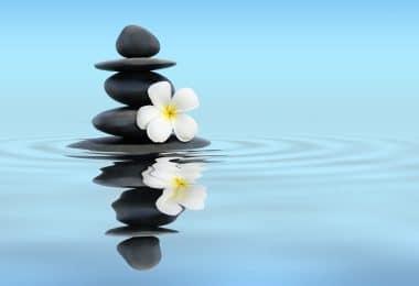 Imagem panorâmica de pedras empilhadas , ao lado de uma flor branca, em um lago, representando a harmonia e tranquilidade.