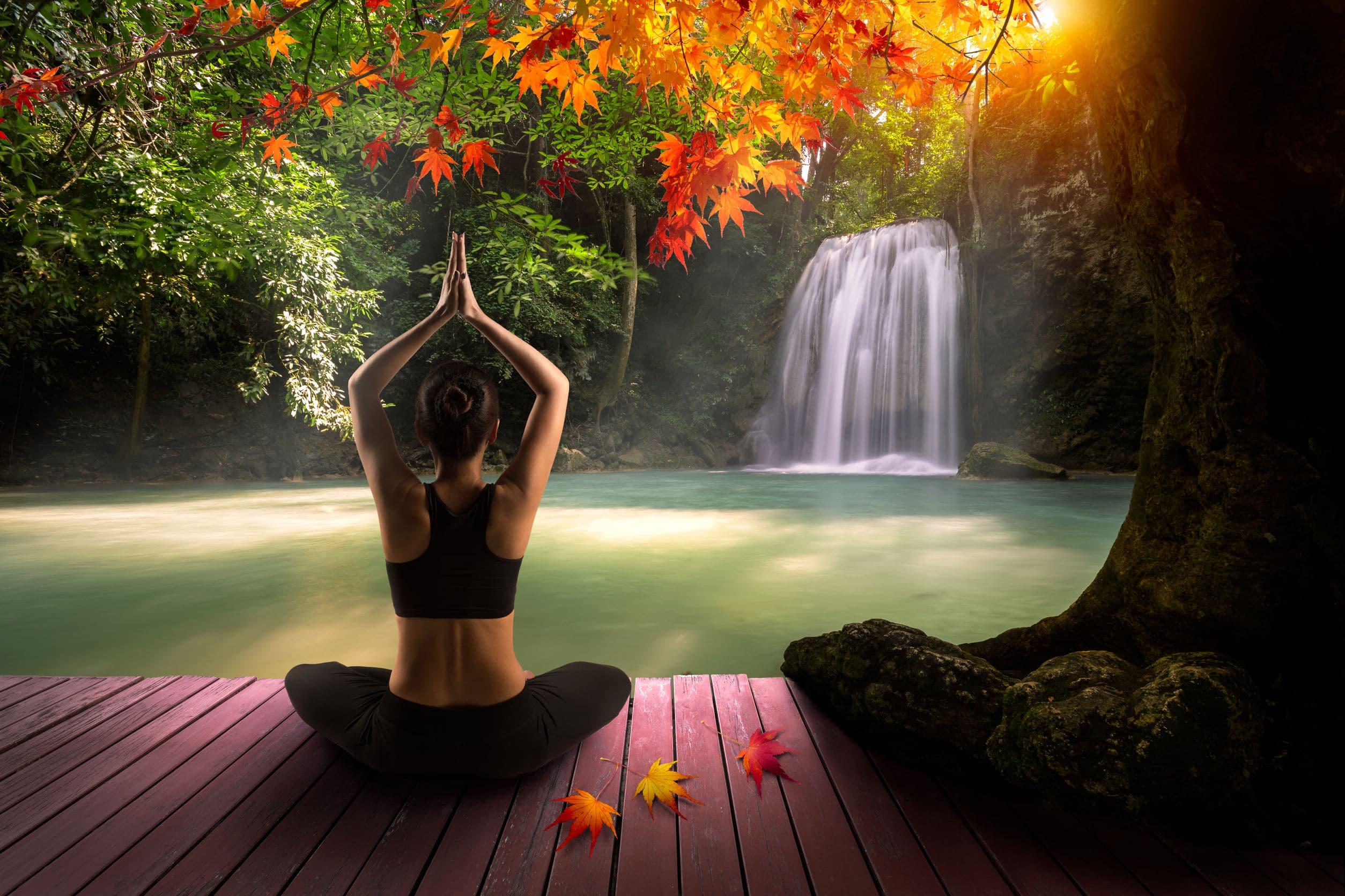Mulher praticando yôga em frente a uma cachoeira.