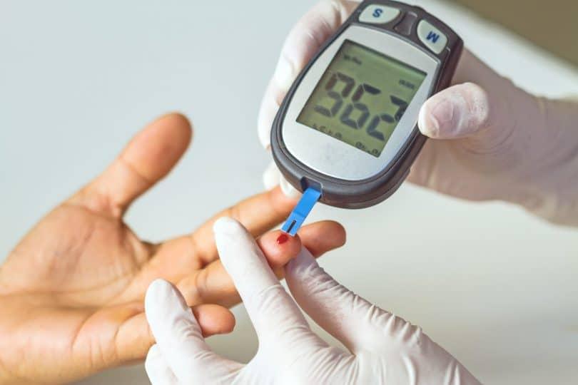 Medidor de glicose em mão de paciente diabético