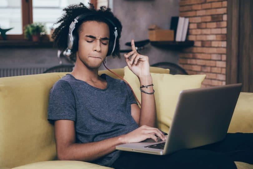 Homem ouvindo música de fone com laptop no colo