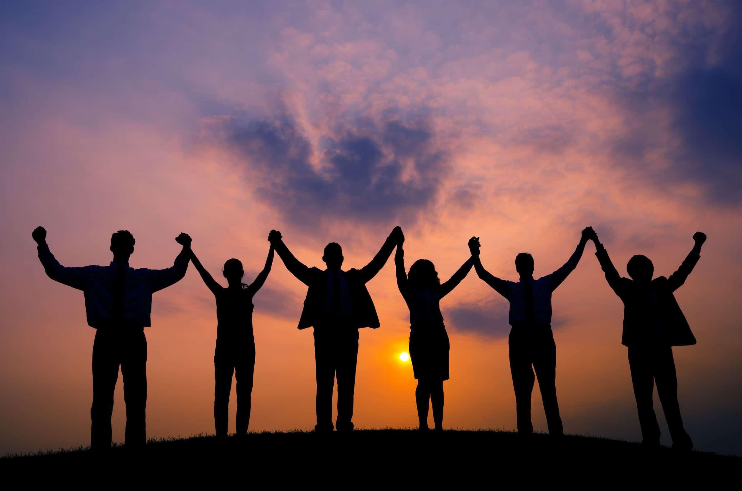 Silhueta de seis pessoas com as mãos dadas ao alto.
