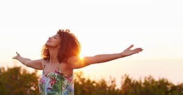 Mulher expressando liberdade ao ar com os braços para cima