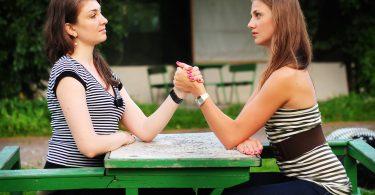 Duas mulheres em queda de braços sentadas em mesa de parque