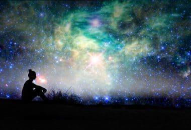 Silhueta de uma mulher sentada com fundo de noite estrelada