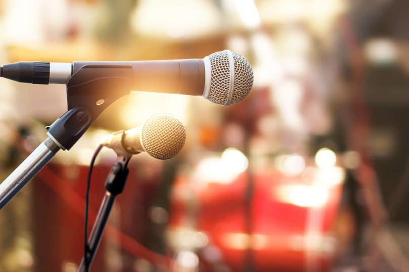 Foto close de dois microfones colocados em cima de um palco, representando a comunicação.