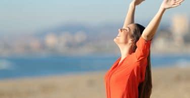 Foto de mulher feliz, jovem, com os braços para cima, em uma praia. Representando liberdade e autonomia.