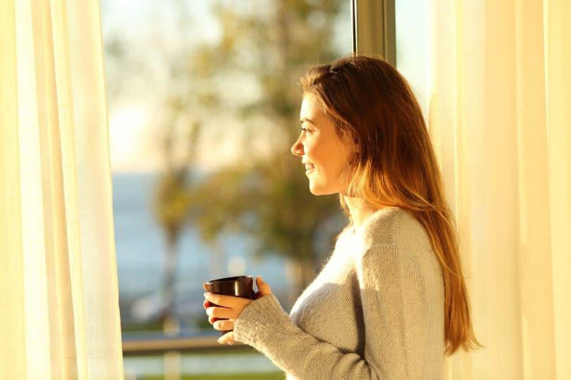 Mulher olhando pela janela com sol refletindo segurando xícara de café