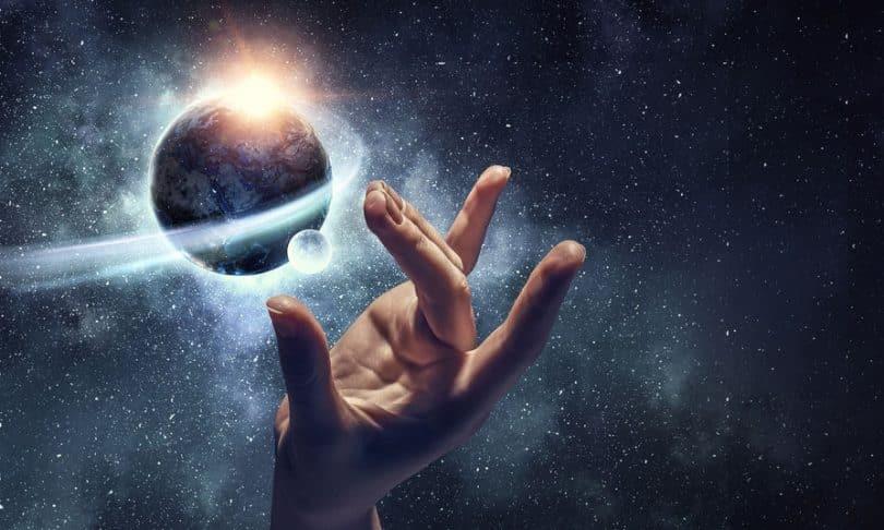 Mão no universo com planeta Terra e luz entre eles