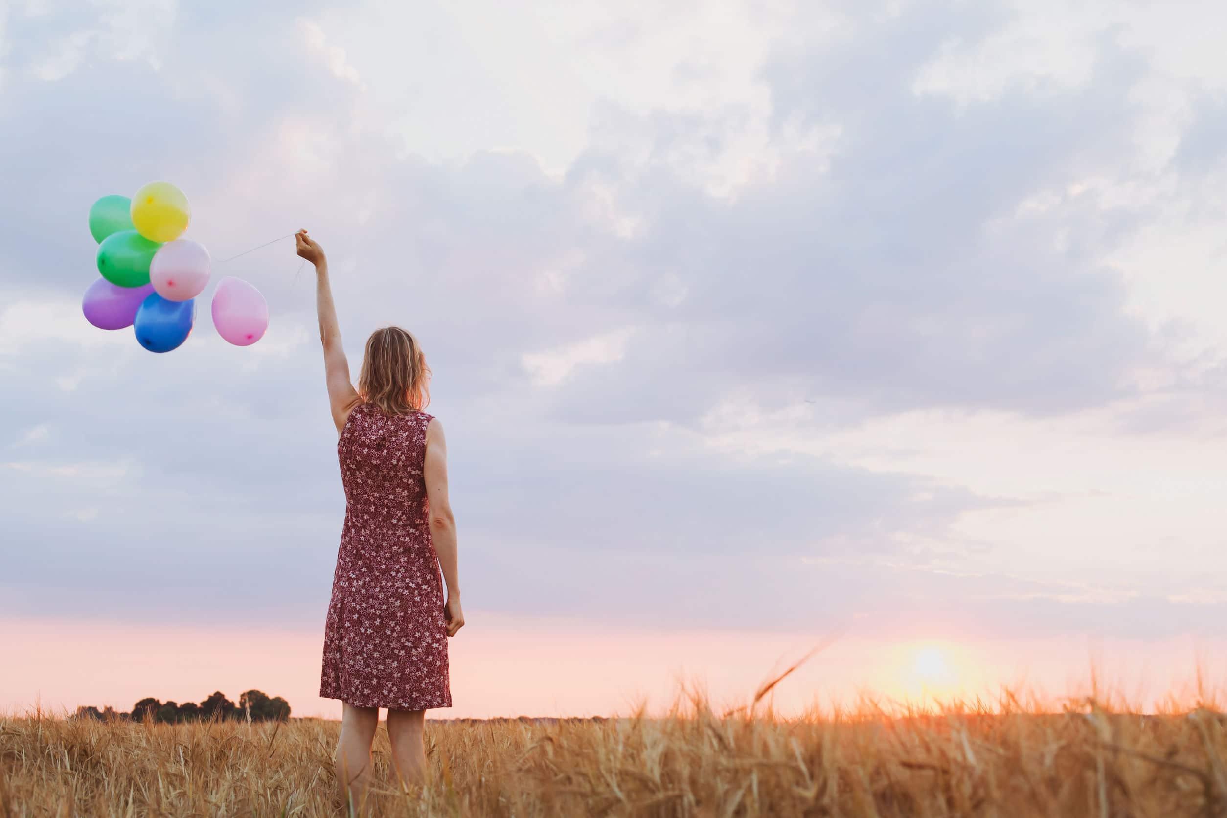 Mulher segurando para o alto barbante com balões coloridos.