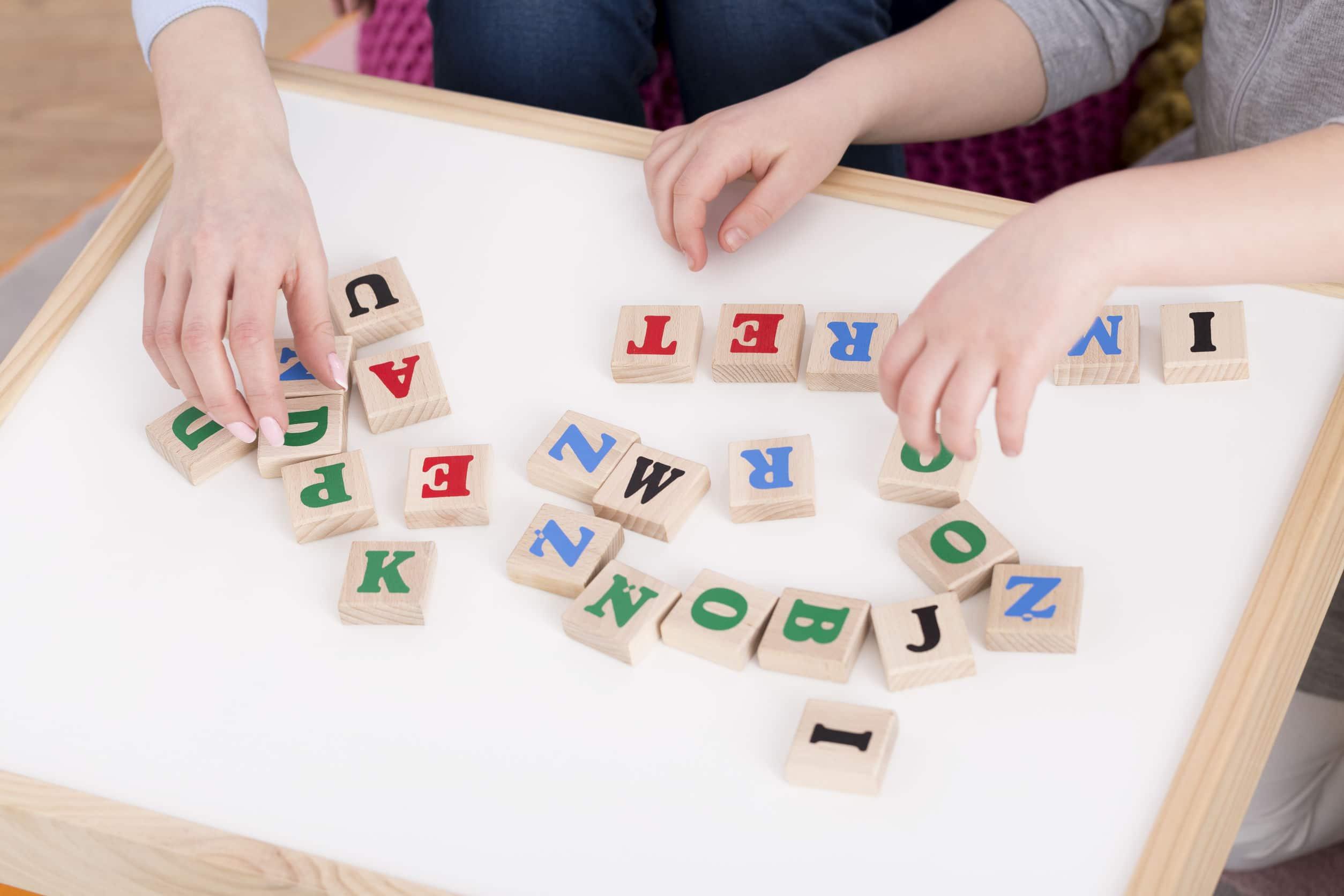 Tabuleiro de letras coloridas sobre uma mesa branca.