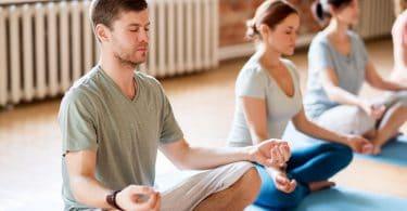 Homem em foco meditando em posição de lótus
