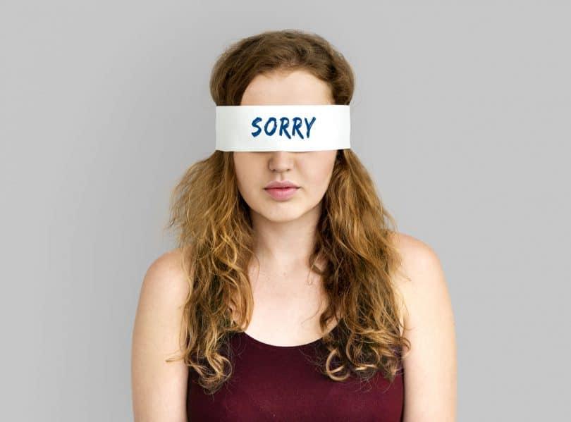 """Mulher com uma venda nos olhos escrito """"sorry""""."""