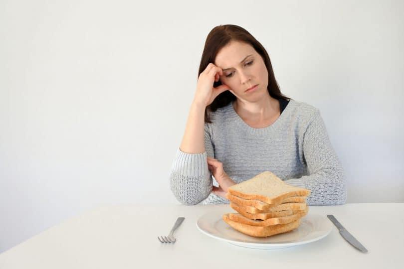 Mulher jovem, branca, triste, vestindo um moletom cinza, sentada em uma mesa, olhando para um prato cheio de fatias de pães.