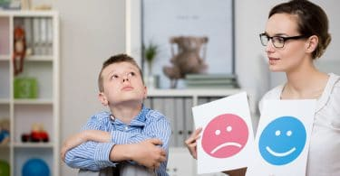 Menino triste em um escritório de psicóloga, que esta segurando duas folhas, uma com uma cara feliz e uma cara triste