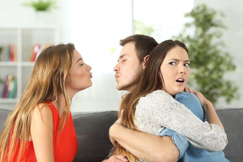 Homem jovem branco, abraçado à sua namorada, também branca e jovem, e, ao mesmo tempo, tentando beijar outra menina, também branca e jovem. Todas as pessoas estão sentadas no sofá de uma sala.