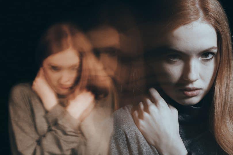 Mulher com mãos perto do rosto com imagem distorcida ao fundo