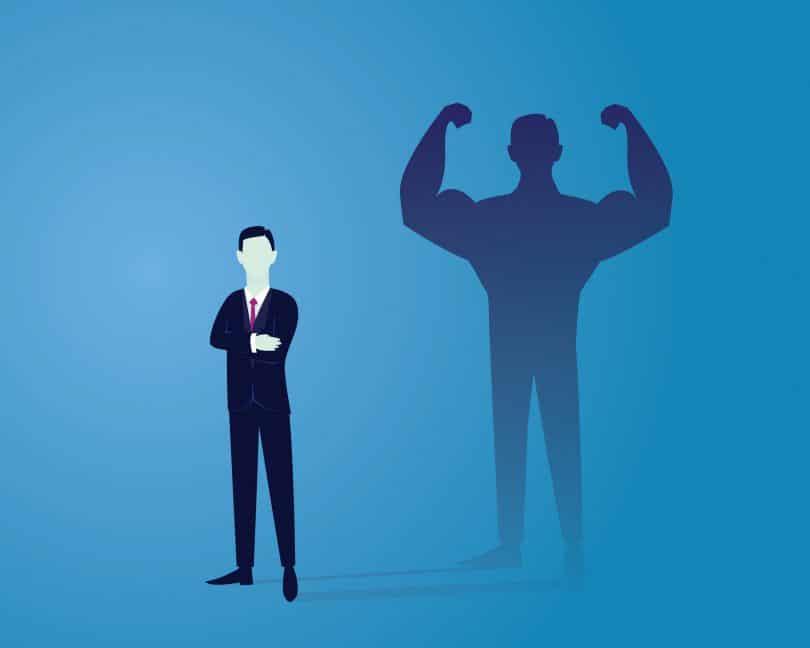 Ilustração vetorial de homem de negócios, vestindo terno, em pé perto de uma parede azul, em frente à silhueta de sua sombra que está com mais músculos, representando a autoconfiança e força.