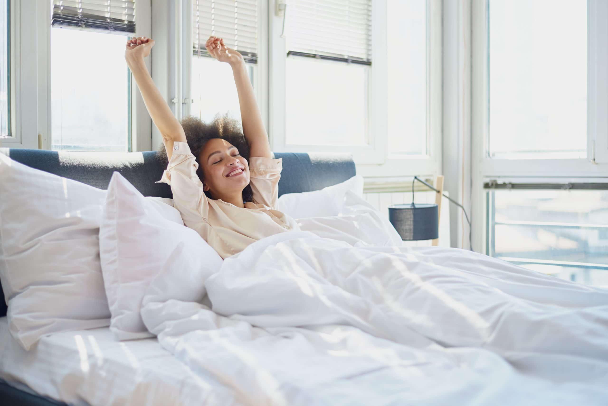 Mulher se espreguiçando na cama.