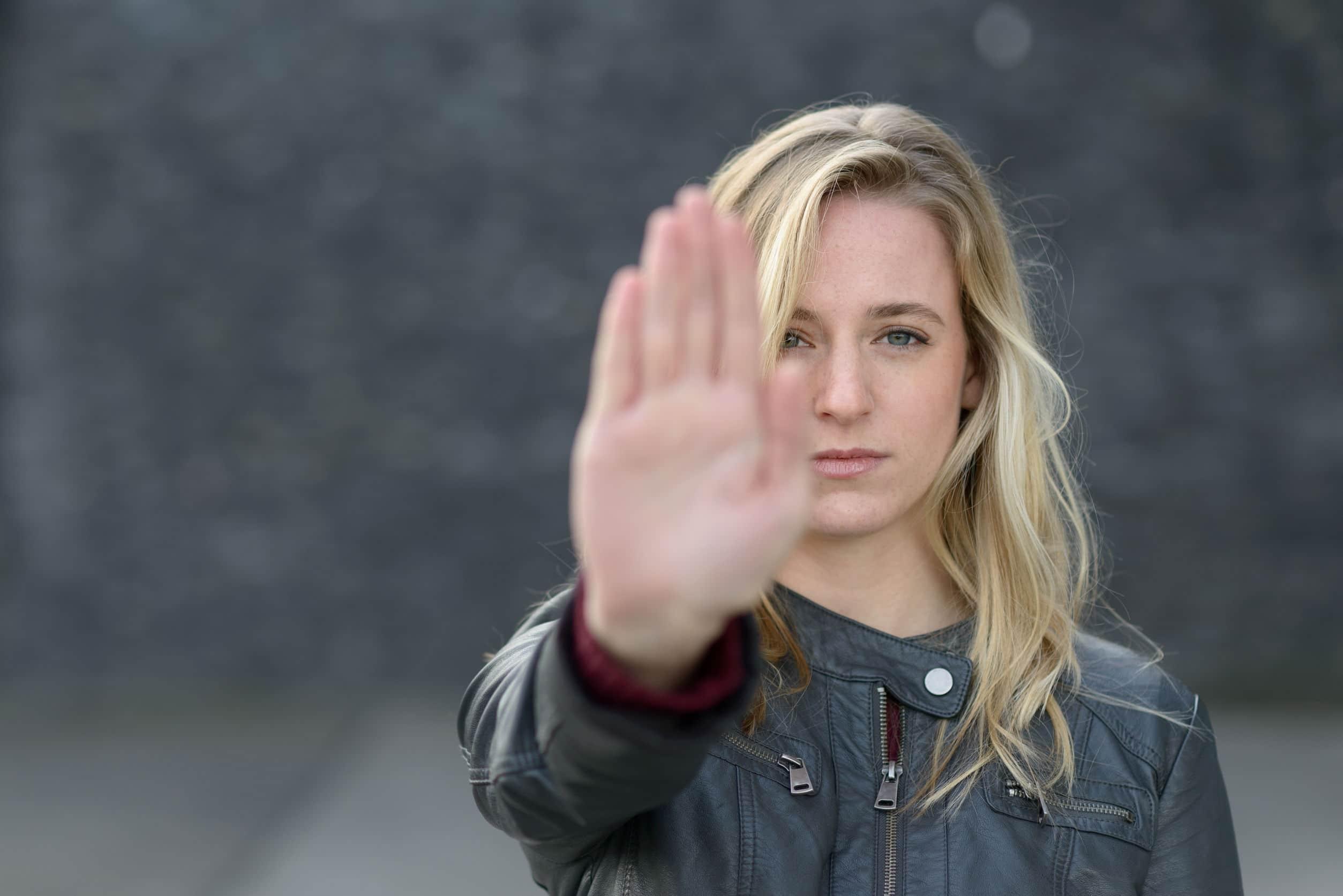 Mulher fazendo sinal de 'pare' com as mãos.