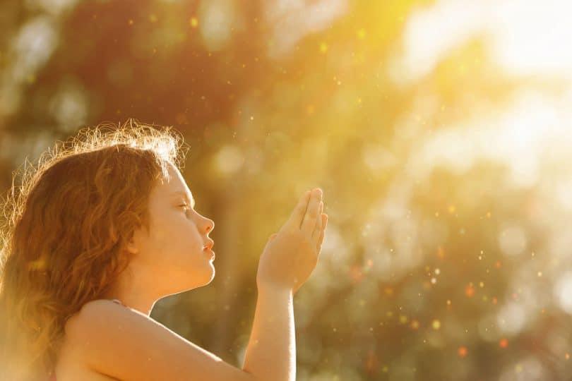 Criança iluminada pelo sol com mãos para o alto