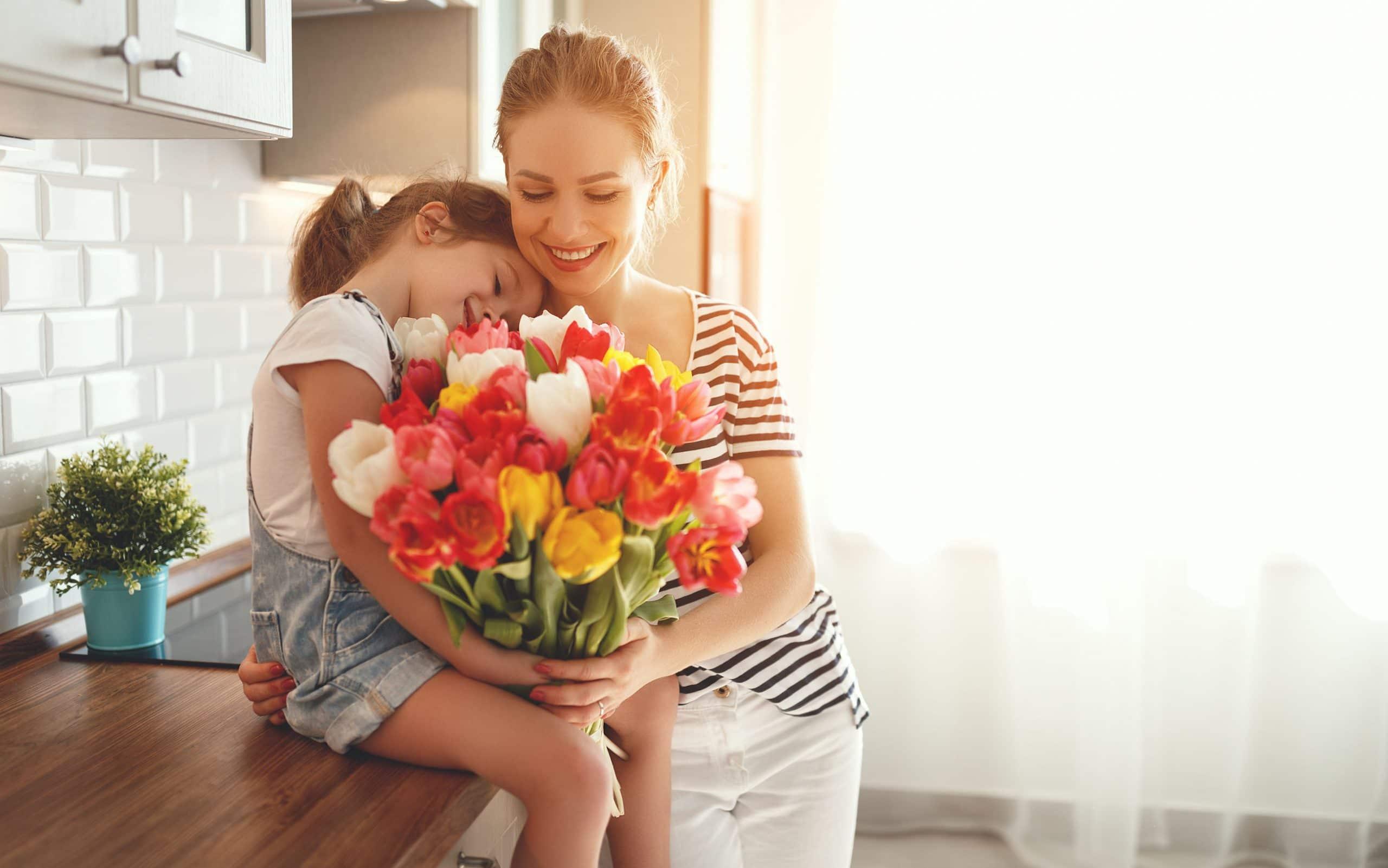 Mãe e filha segurando um buquê de flores.