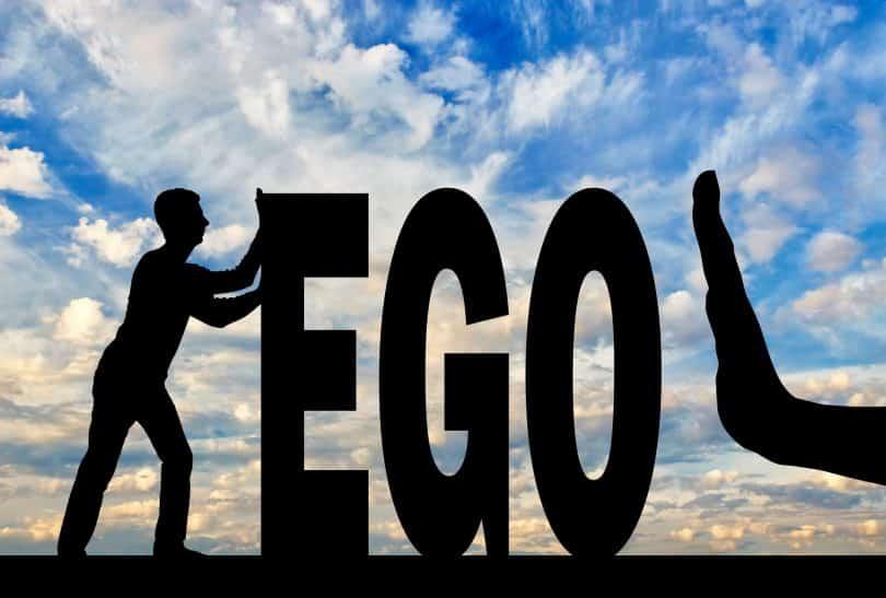 Gesto de parada da mão e silhueta do homem empurrando a palavra ego.