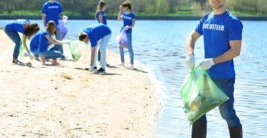 Grupo de voluntários, todos vestindo camisetas azuis, recolhendo lixo da areia da praia, segurando sacos de lixo.