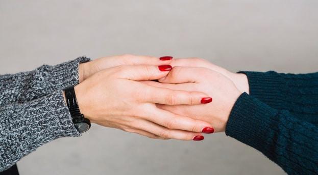 Dois pares de mãos femininas segurando uma a outra.