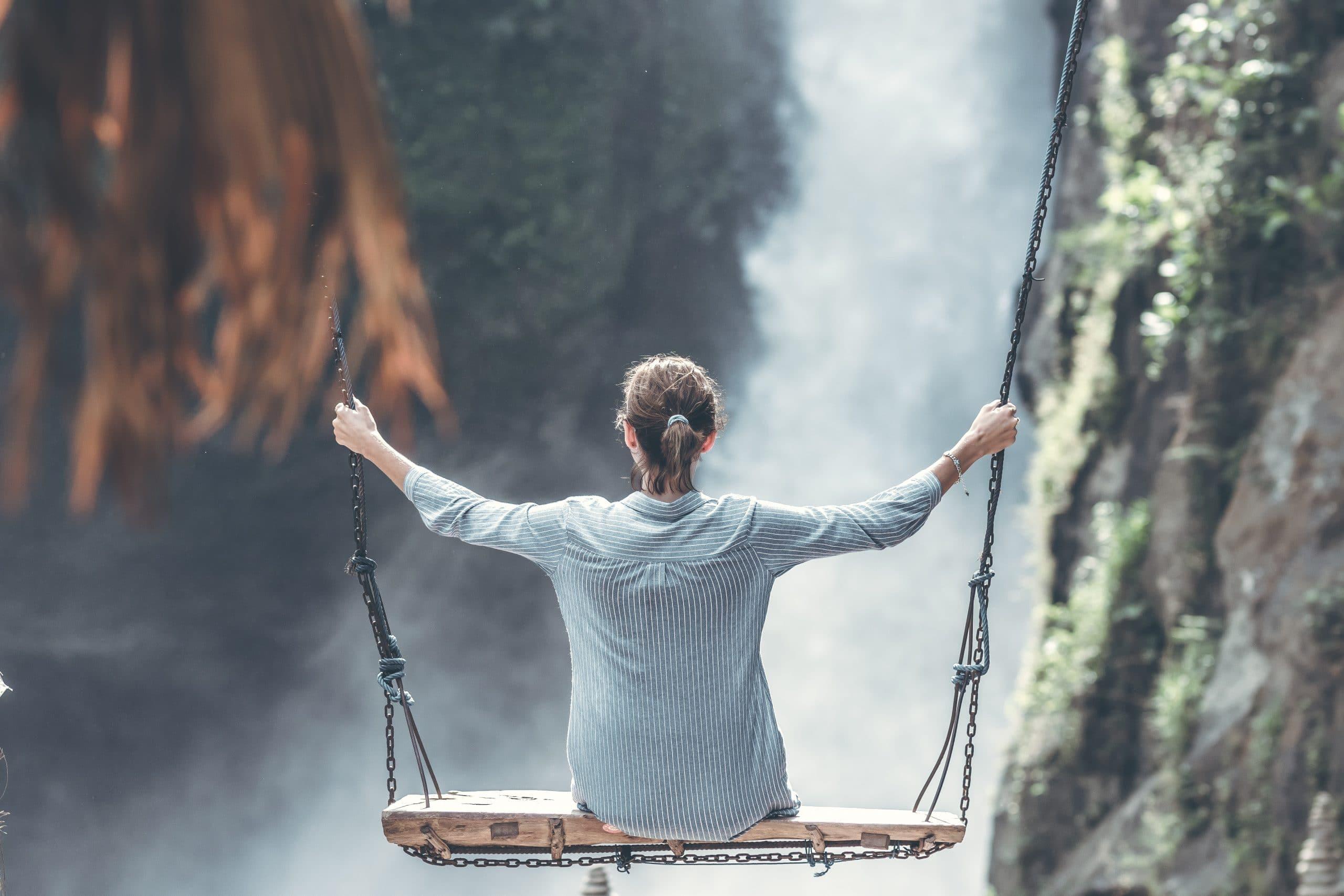 Mulher em balanço de madeira com cachoeira ao fundo